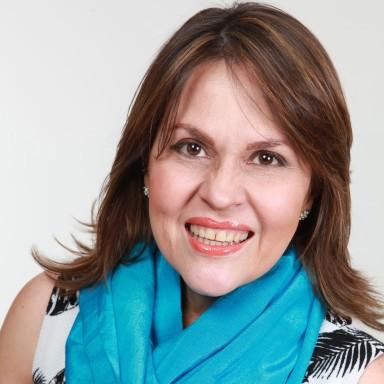 Mujer sonriente conferencista maru pacheco lleva una bufanza azul en el cuello