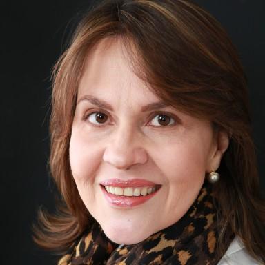 mujer sonriente con bufanda en el cuello conferencista de make it happen maru pacheco