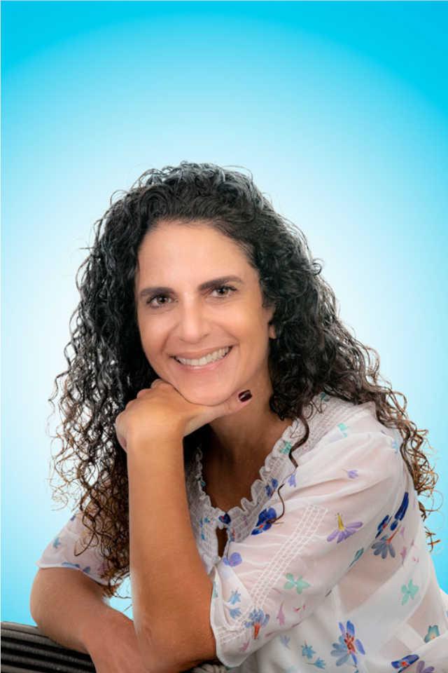 mujer sonriente con la mano en la quijada cabello suelto en fondo azul claro