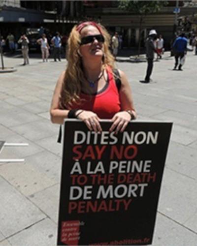 mujer de cabello largo rubio suelto con letrero de activista de derecho humano belen vallenilla