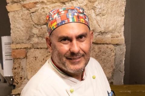 hombre moreno claro con corta chiva lleva un traje de chef y gorro de su cabeza con banderas de países historia que contar Alberto Frewa