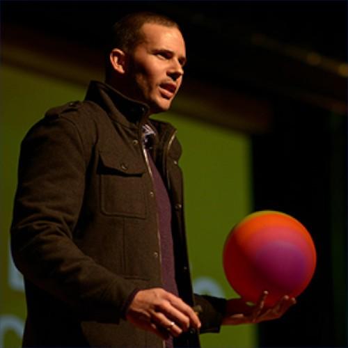 hombre que lleva una linda chaqueta maron y sus mano una pelota rosada con fuscia conferencista carlos fernandez