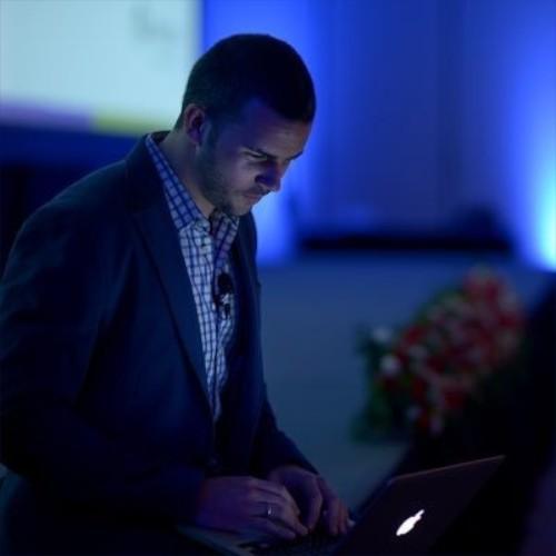 hombre joven que lleva puesto traje azul tiene al frente una tablet en una conferencia carlos fernandez