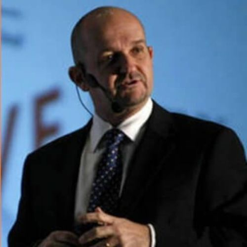 hombre de traje negro con corbata azul con microfono en su cara luis maturen conferencista de liderazgo en el siglo xxi