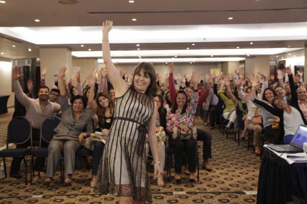 mujer conferencista maru pacheco con el brazo derecho en alto, detras tiene aun grupo de personas con las manos arriba señal de triunfo