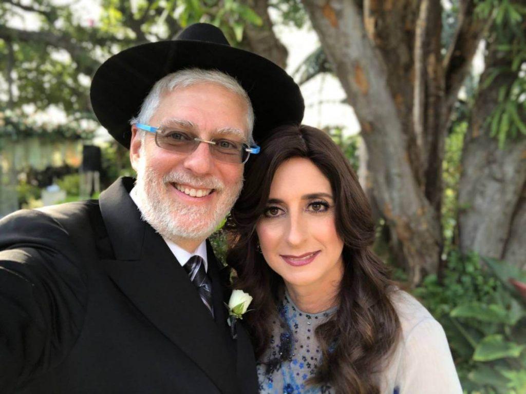 hombre sonriente y con barba blanca con traje y sombrero negro de rabino al lado tiene a un mujer hermosa con cabello largo alex y raquel gutt