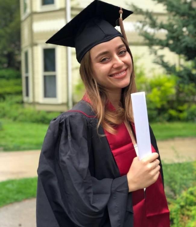 señorita sonriente que lleva un diploma en sus manos de una graduacion con toga y birrete Dalit Merenfeld en su graduación de Kell School of Business Indiana University en 2019