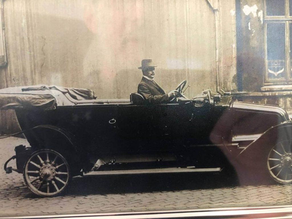 foto antigua de un hombre que lleva un traje negro y sombrero sentado en un carro antiguo negro elegante Efim Warchaski en Hamburgo Alemania