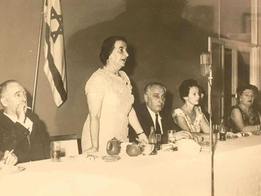 una mesa con personas sentadas reunidas en un vento bnei brithay una mujer parada y al lado tiene la bandera de israel