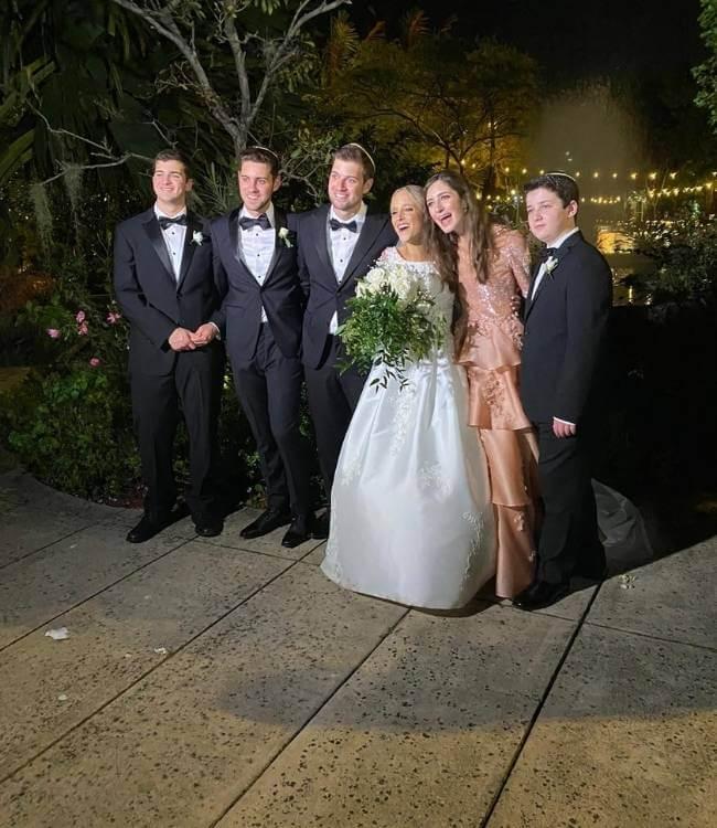 4 caballeros vestidos de elegante traje de color negro con una chica vestida de blanco con rams de flores en las manos