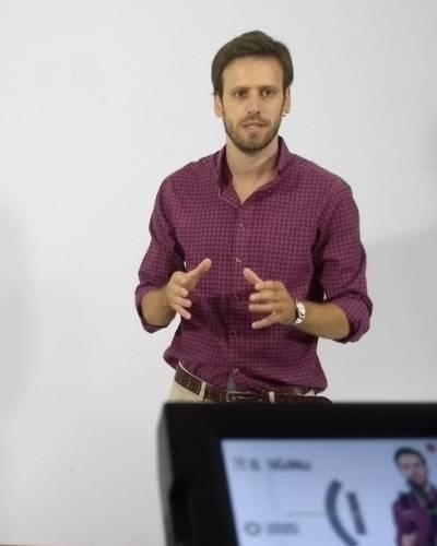 hombre joven con camisa de cuadrados de pie con las manos adelanto dando una conferencia hay un monitor que lo enfoca agustin remondino