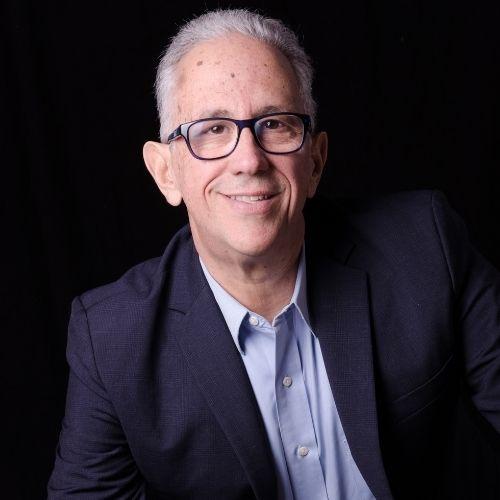 hombre sonriente con traje oscuro y lente en sus ojos conferencista carlos rosales