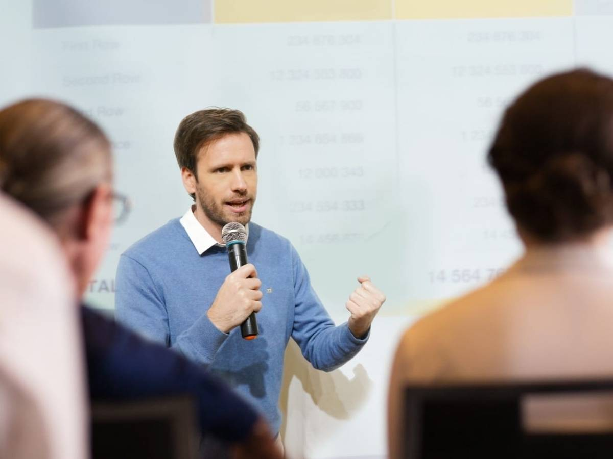 hombre joven con microfono en la mano dictabdo una conferencia