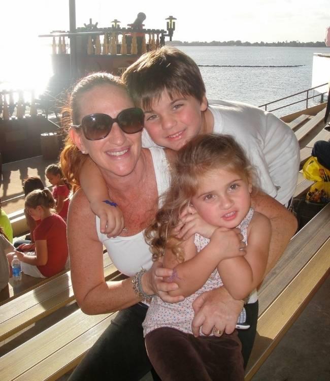 Mujer con lente oscuro en los ojos abrazada de dos hermosos niños que son sus hijos Junto a Eitan y Mijail