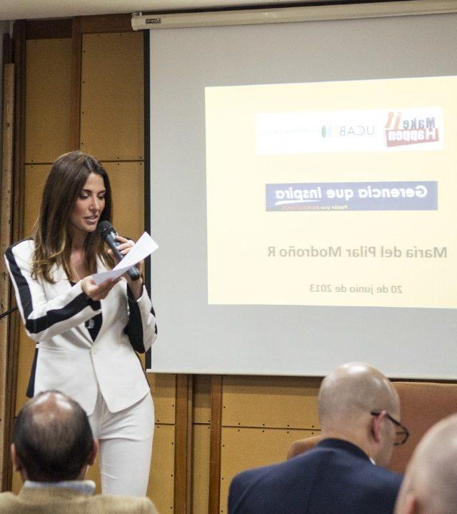 mujer conferencista elegante con traje blanco y microfono en una de sus manos evento make it happen a un grupo de personas