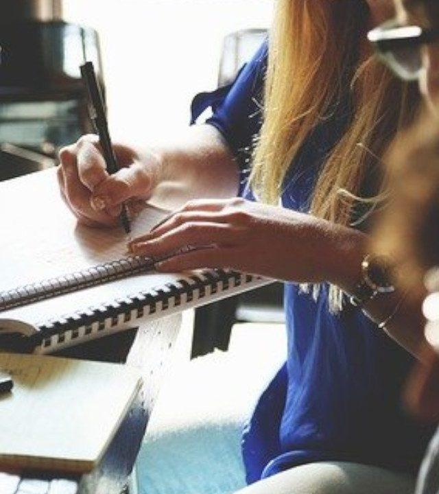 mujer con cabello largo rubio con pluma en la mano y un cuaderno organizando conferencista