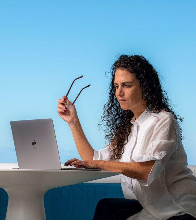 mujer con camisa blanca sentada con lente en su mano derecha una lapto al enfrente proximo encuentros que inspiran tamara kassab